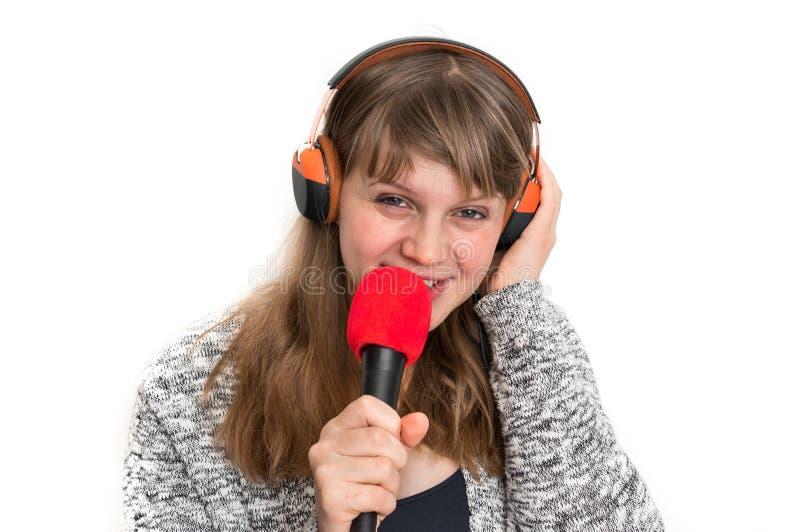 Женщина с mic и наушниками записывает ее песню стоковые фото