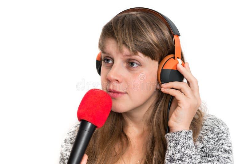 Женщина с mic и наушниками записывает ее песню стоковые изображения