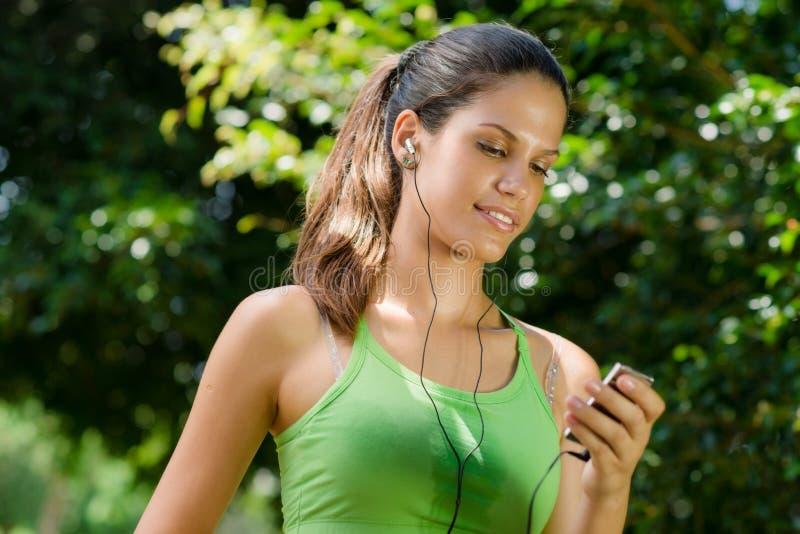 Женщина с mp3 плэйер слушая к нот стоковые изображения