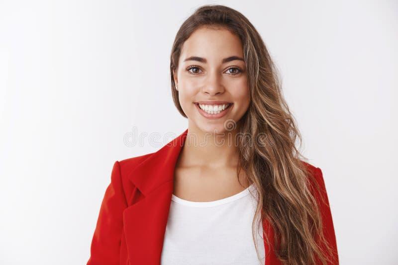 Женщина талии-вверх успешная удачливая привлекательная европейская нося зубы красной куртки усмехаясь белые оставаясь положительн стоковые фотографии rf