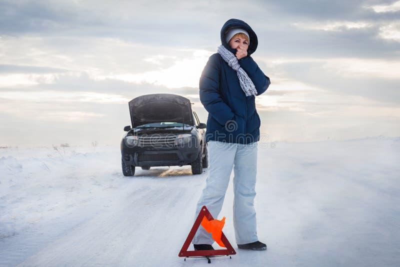 Женщина теет холодные руки Ей холодно Зима Знак остановки экстренного вызова стоковое фото