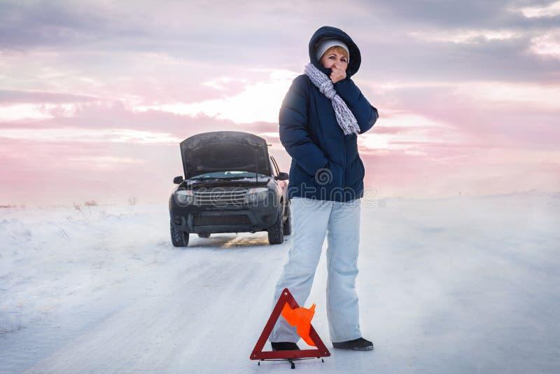 Женщина теет холодные руки Ей холодно Зима Знак остановки экстренного вызова стоковые фото