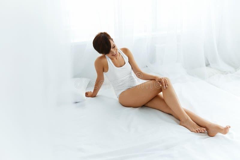 Женщина тела красоты Красивая девушка касаясь ногам Epilated длинным стоковое фото rf
