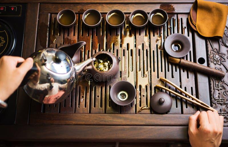 Женщина традиционно подготавливая китайский чай в церемонии чая стоковые изображения