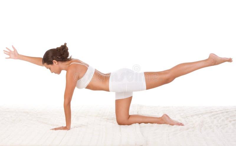 женщина тренировки выполняя йогу представления стоковое фото