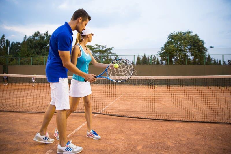 Женщина тренировки человека для того чтобы сыграть теннис стоковая фотография