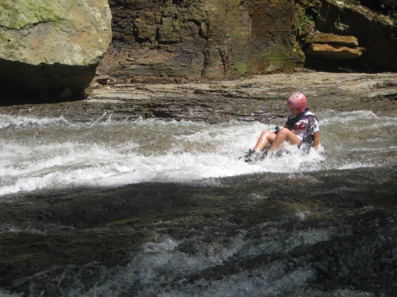 Женщина туриста сползая камнями водопада в Barinas Венесуэле в Южной Америке стоковое изображение
