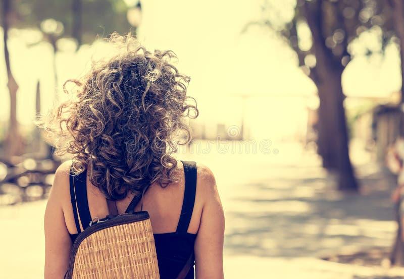 Женщина увиденная от задней части с расплывчатой предпосылкой стоковая фотография rf