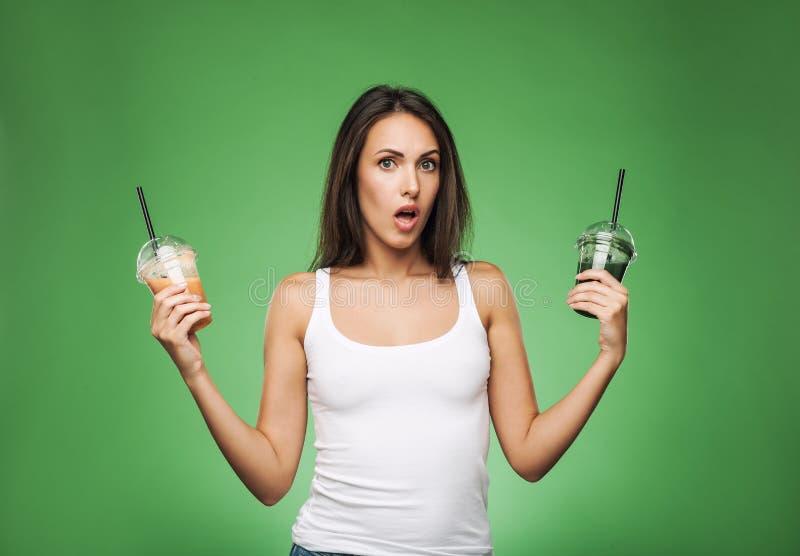 Женщина удивленная детенышами держа smoothie стоковое изображение