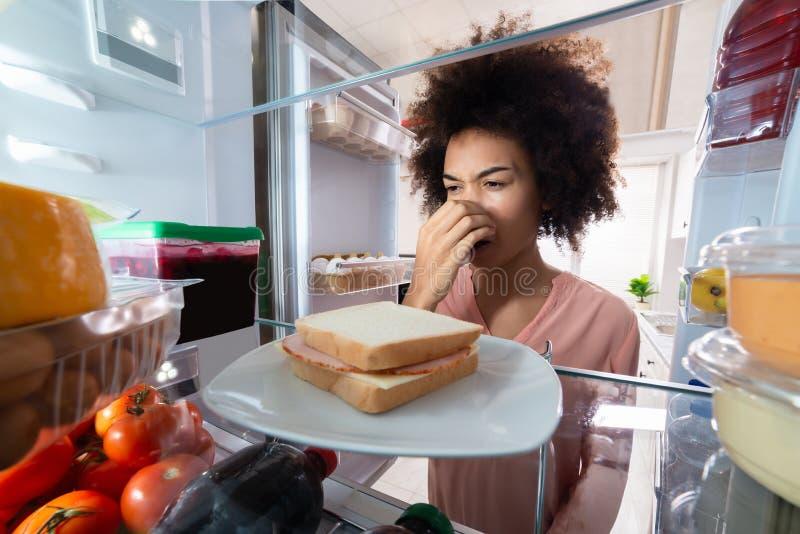 Женщина узнавая плохой запах от сэндвича с ветчиной стоковое фото rf