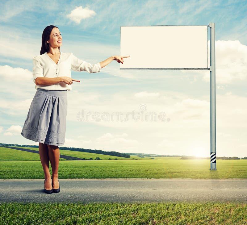 Женщина указывая на пустую белую афишу стоковые изображения rf