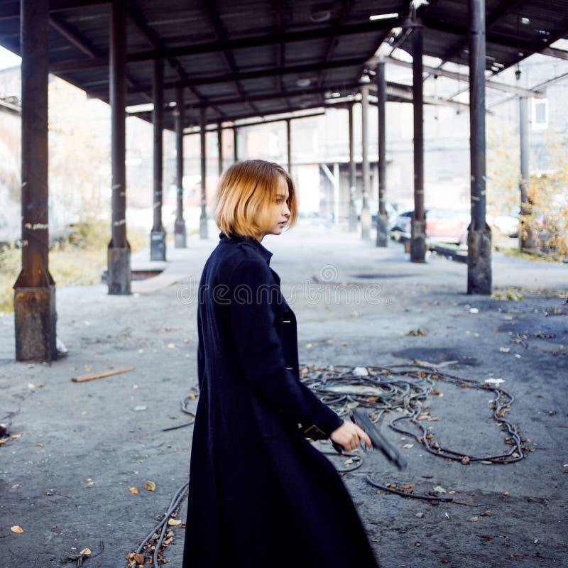 Женщина указывая оружие Женщина стоит с пистолетом в руке стоковое фото rf