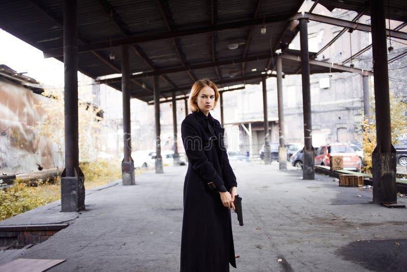 Женщина указывая оружие Стрельба девушки мафии на кто-то на улице стоковое изображение