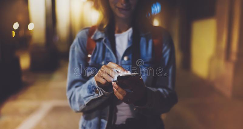 Женщина указывая палец на smartphone пустого экрана на свете bokeh предпосылки в городе ночи атмосферическом, битнике блоггера ис стоковое фото
