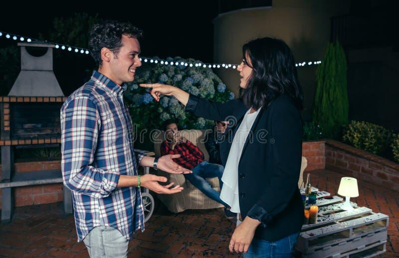 Женщина указывая с пальцем к усмехаясь человеку в партии стоковая фотография