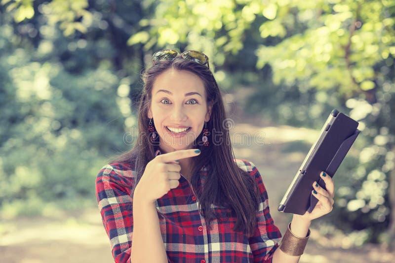 Женщина указывая с пальцем на ее компьютер пусковой площадки стоковая фотография