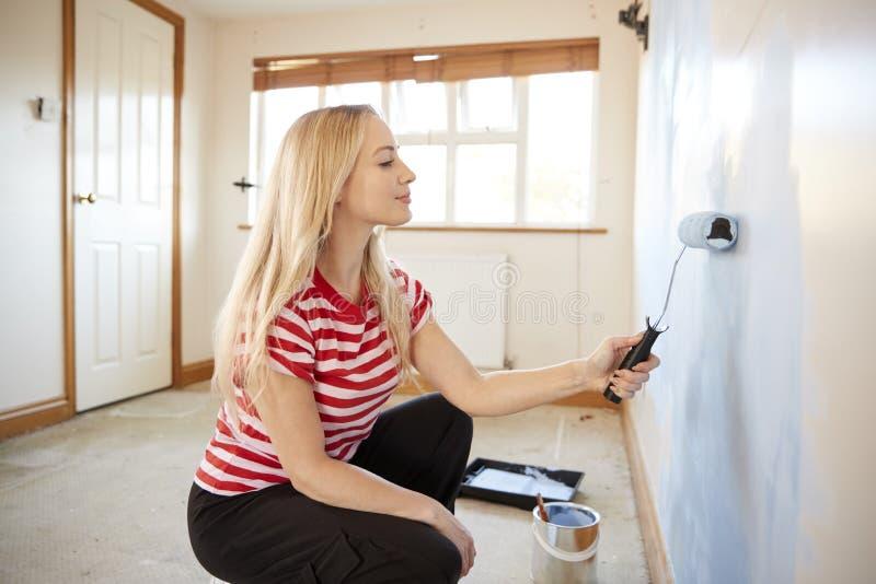 Женщина украшая комнату в новой домашней крася стене с роликом стоковые изображения rf