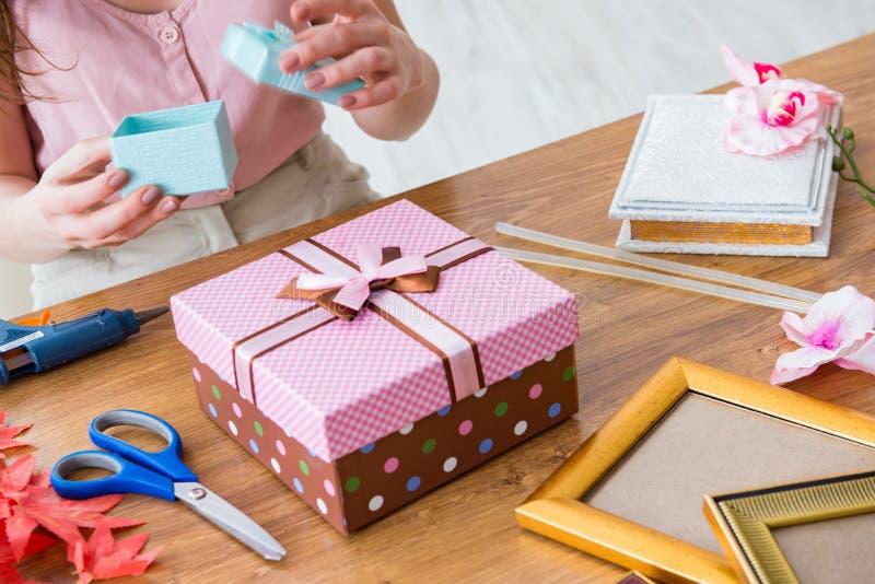 Женщина украшая подарочную коробку для специального случая стоковые фото