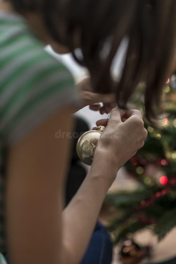 Женщина украшая рождественскую елку с золотой безделушкой стоковое изображение rf