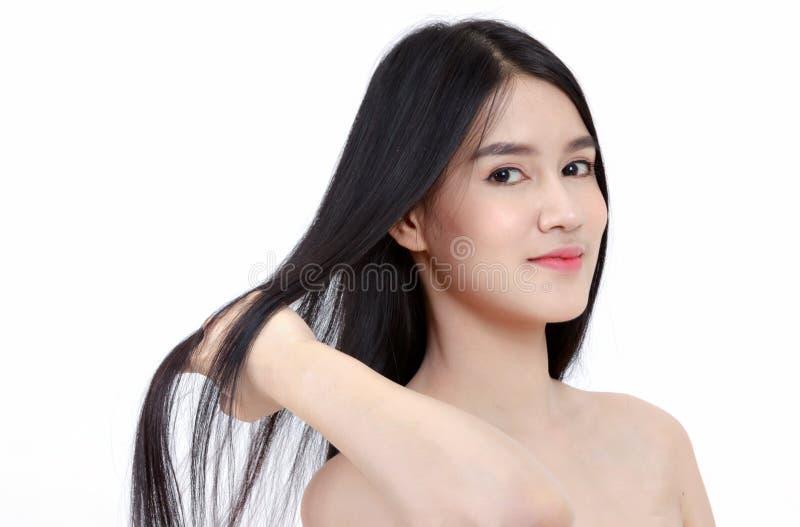 женщина улыбки азиатская касается ее волосам здоровья длинным прямым, щеголю стоковое фото rf
