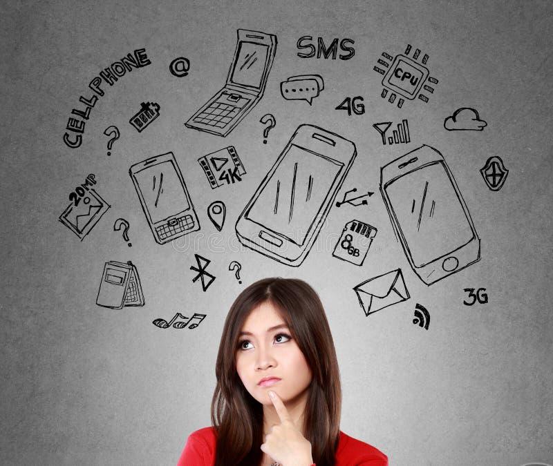 Женщина думая о каком телефоне для того чтобы купить стоковые изображения