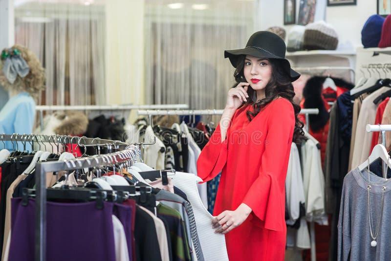 Женщина думая что одеть, ходящ по магазинам стоковое фото