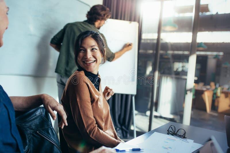 Женщина усмехаясь во время представления дела в офисе стоковое изображение rf
