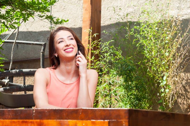 Женщина усмехаясь и говоря на телефоне внешнем стоковое изображение rf