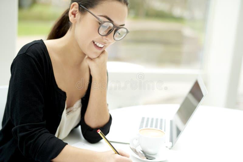 Женщина усмехаясь и писать в блокноте стоковые изображения rf