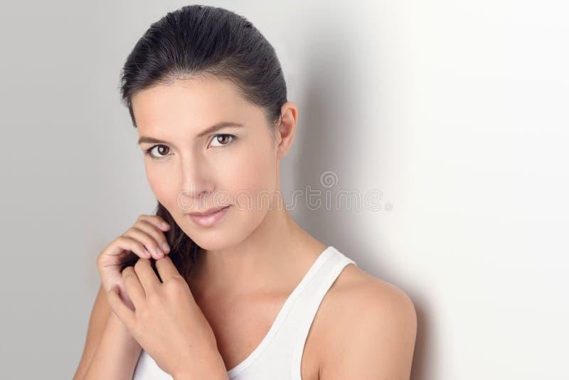 Женщина усмехаясь на камере пока держащ ее волосы стоковые изображения rf