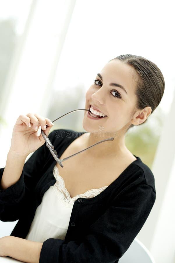 Женщина усмехаясь на камере сдерживая на руке eyeglass стоковое изображение