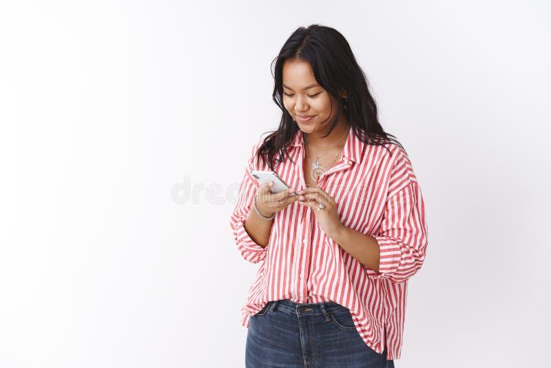 Женщина усмехаясь нежно читающ прекрасное сообщение от смартфона удерживания девушки grinning на экране мобильного телефона стоковое изображение rf