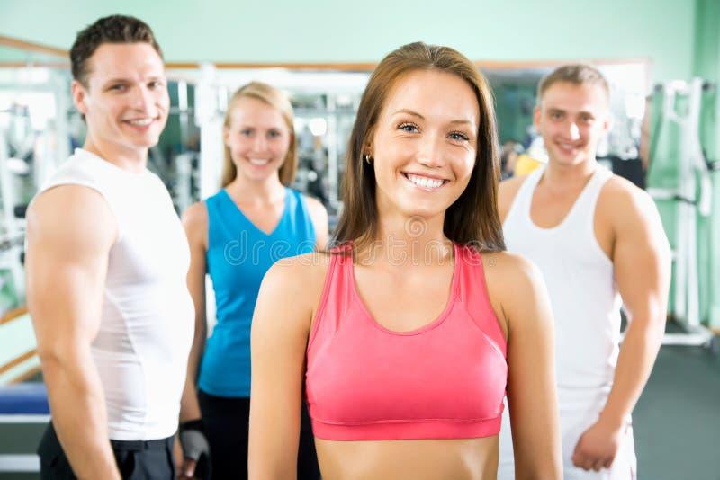 Женщина усмехаясь перед группой в составе люди спортзала стоковое изображение