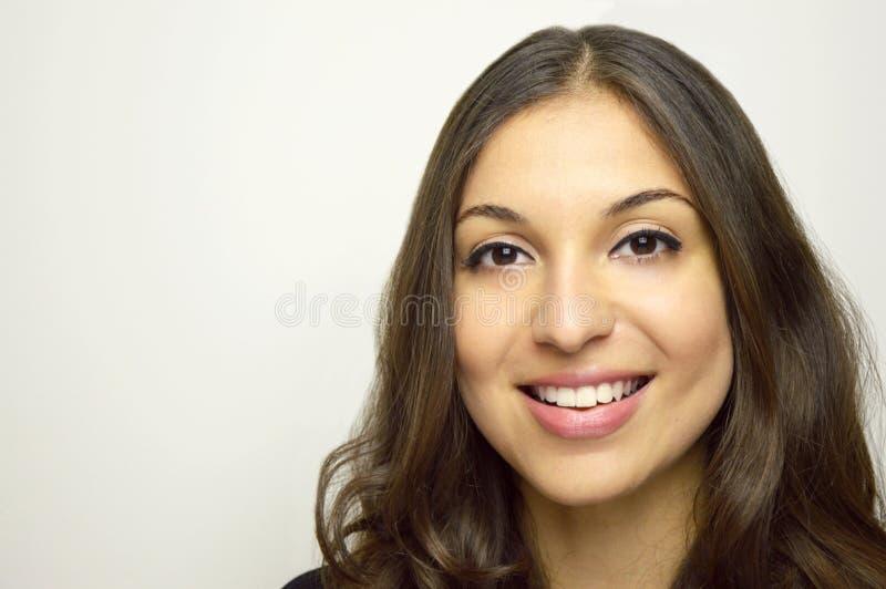 Женщина усмехаясь с совершенной улыбкой и белыми зубами и смотря камеру на серой предпосылке стоковые изображения rf