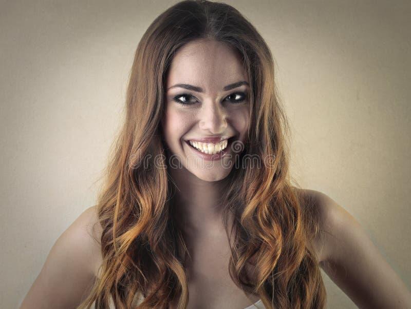 Женщина усмехаясь широко стоковое фото