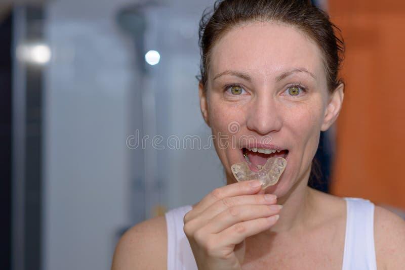 Женщина устанавливая плиту укуса в ее рте стоковое изображение rf