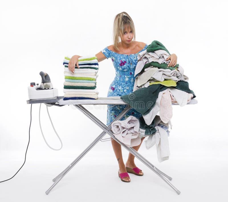 Женщина утюжа на много одежду стоковое фото