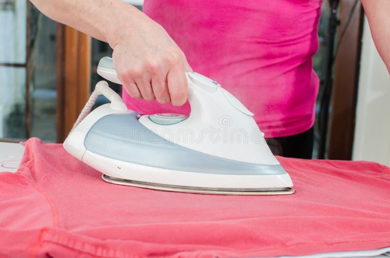 Женщина утюжа футболку стоковое фото