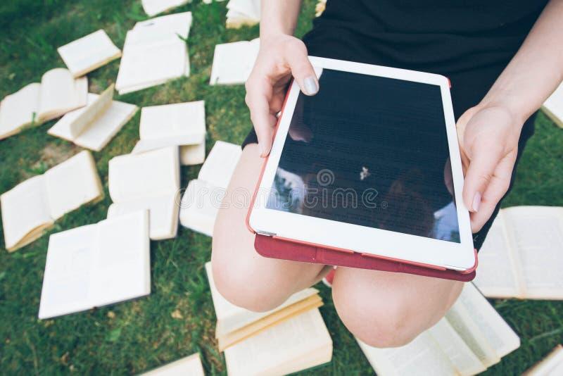 Женщина уча с читателем и книгой ebook Выбор между современной воспитательной технологией и традиционным методом пути Девушка дер стоковая фотография rf