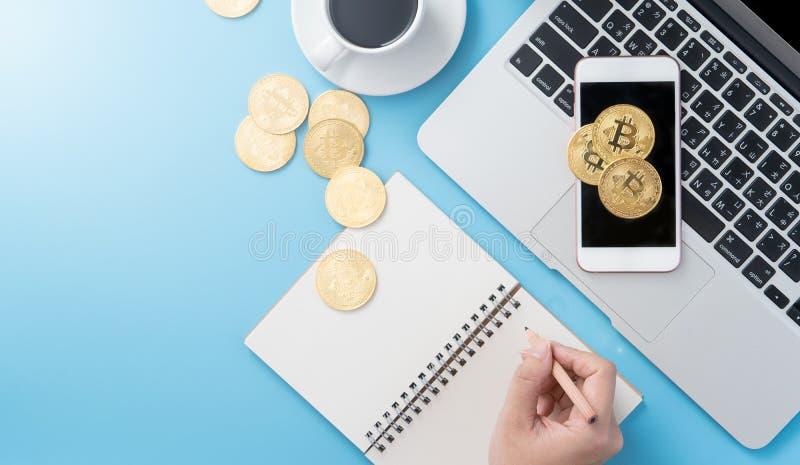 Женщина учитывающ концепция денег изолируется на столе чистого голубого офиса работая с bitcoin и кофейной чашкой, дизайном места стоковые изображения rf