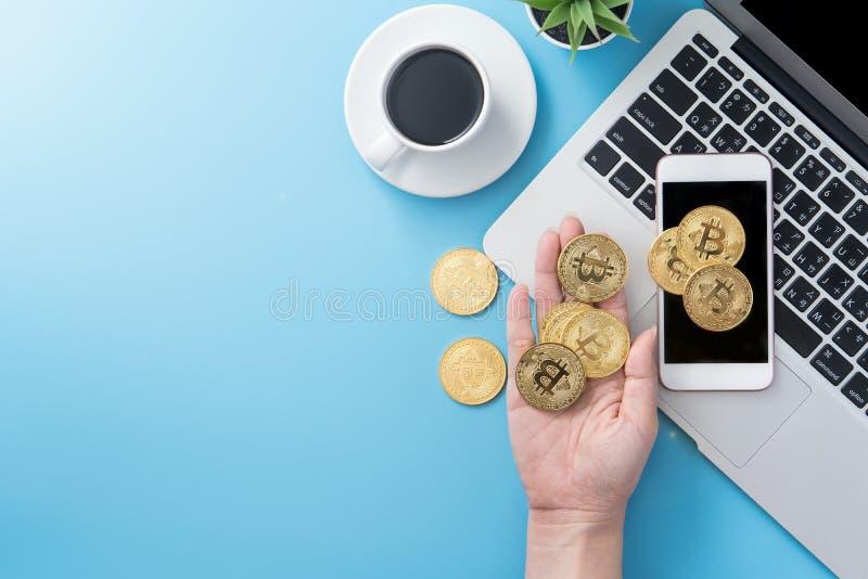 Женщина учитывающ концепция денег изолируется на столе чистого голубого офиса работая с bitcoin и кофейной чашкой, дизайном места стоковое фото