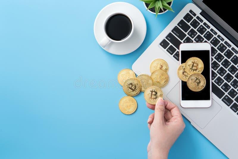 Женщина учитывающ концепция денег изолируется на столе чистого голубого офиса работая с bitcoin и кофейной чашкой, дизайном места стоковая фотография