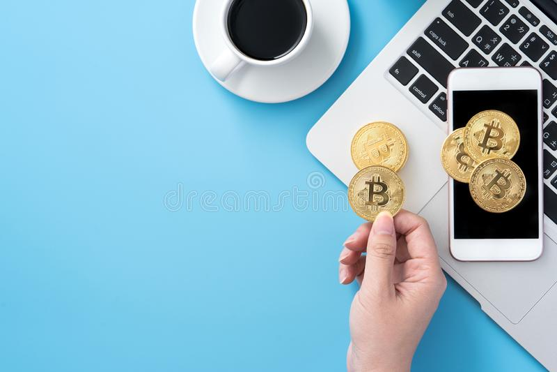 Женщина учитывающ концепция денег изолируется на столе чистого голубого офиса работая с bitcoin и кофейной чашкой, дизайном места стоковые фото