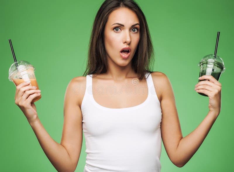 Женщина удивленная детенышами держа smoothie стоковое изображение rf