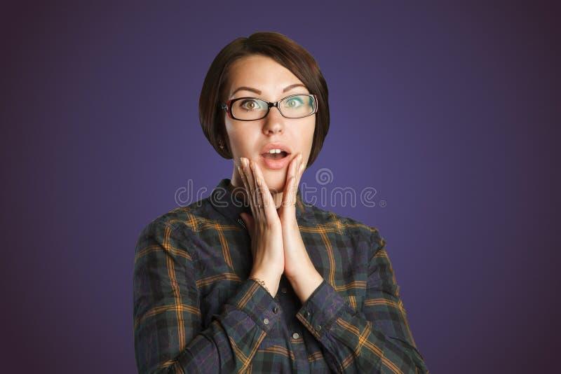 Женщина удивленная красотой изолированная на фиолетовой предпосылке стоковая фотография rf