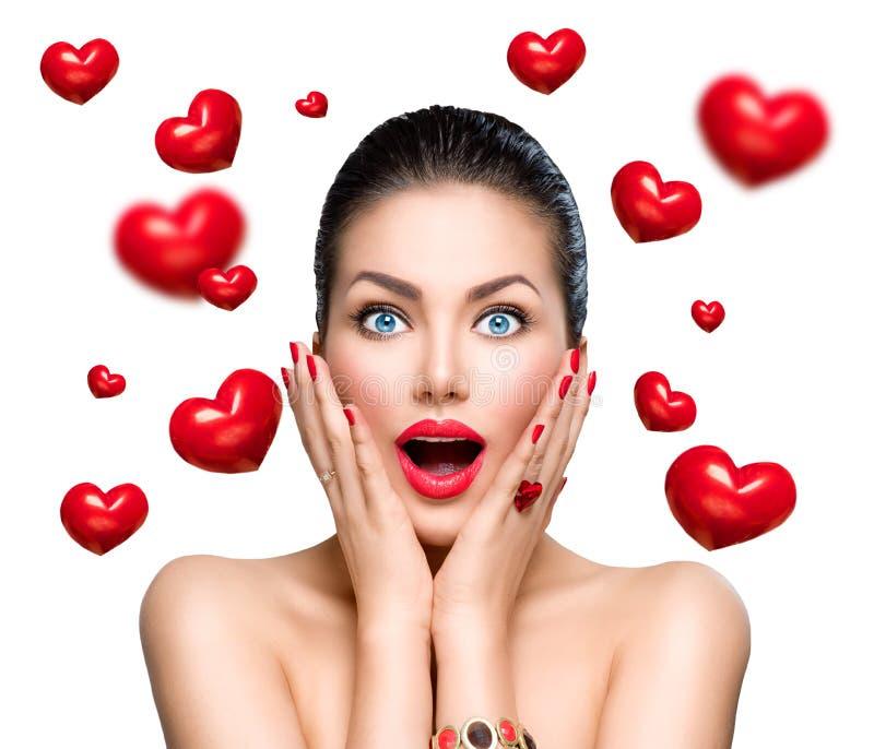 Женщина удивленная красотой с летать красные сердца стоковое изображение rf