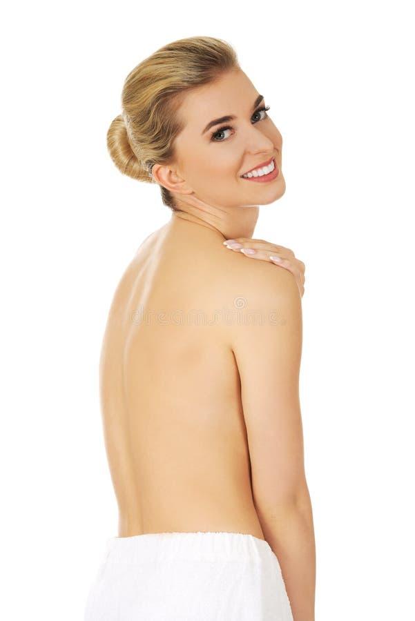Женщина улыбки детенышей топлесс с белым полотенцем вокруг ее талии стоковые изображения rf