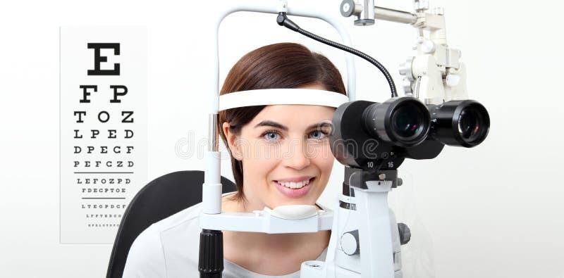 Женщина улыбки делая измерение зрения с разрезанной лампой и visual стоковое изображение rf