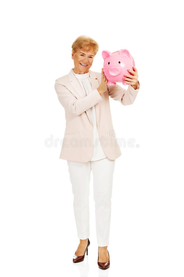 Женщина улыбки пожилая держа копилку стоковая фотография rf