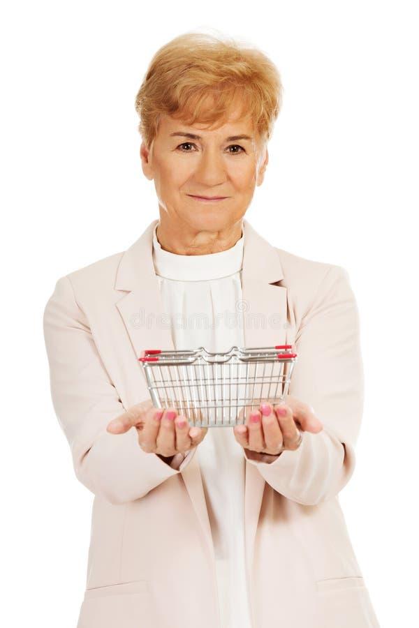 Женщина улыбки пожилая держа малую корзину для товаров стоковое фото